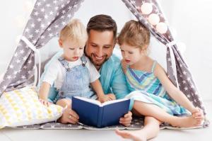 padre-della-famiglia-che-legge-al-libro-di-bambini-tenda-casa-109174039